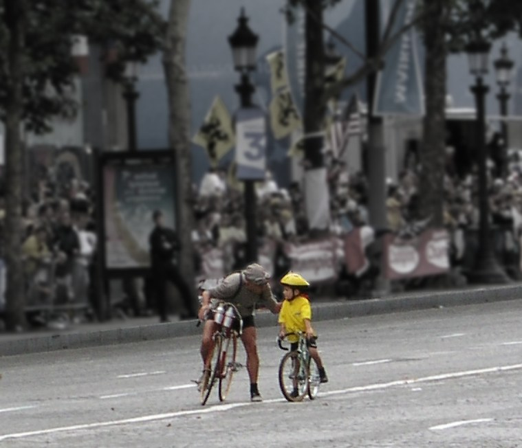 An older road cyclist talking to a very young child on a road bike.